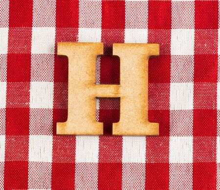 Letter H of the alphabet - Red checkered fabric tablecloth. Standard-Bild