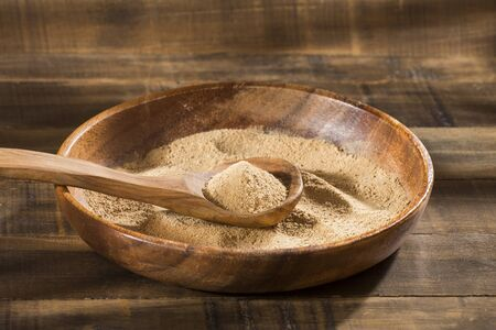 Maca powder in wooden spoon - Lepidium meyenii.