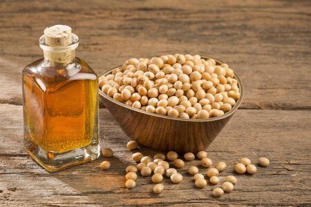 Oil and soybeans - Glycine max. Wooden background