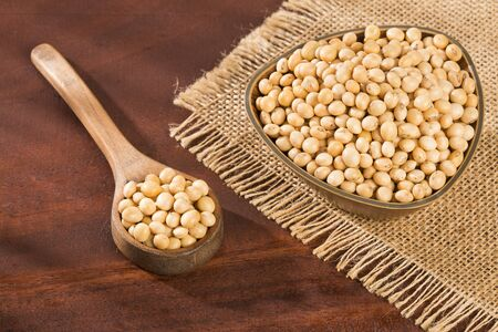 Dry soybeans - Glycine max. Wooden background