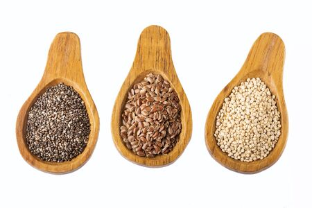 Organic chia, quinoa and flaxseed seeds in wooden spoons Stockfoto