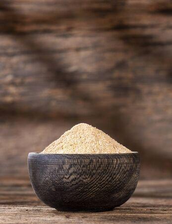 Organic maca root powder in wooden bowl - Lepidium meyenii Stock Photo