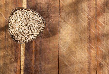 Wooden bowl with pearl barley - Hordeum vulgare