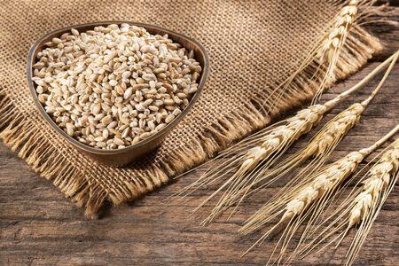 Dried pearl barley in a wooden bowl - Hordeum vulgare