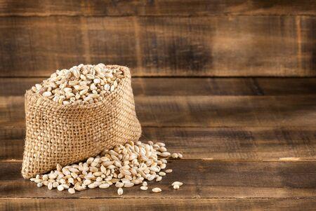 Pearl barley in sack on a wooden table - Hordeum vulgare