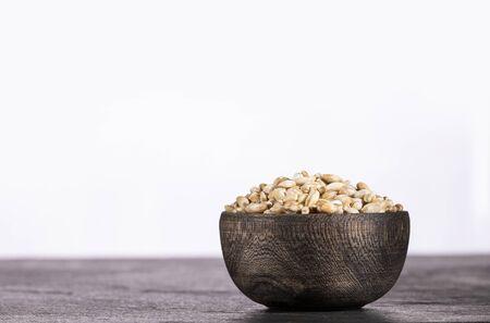 Pearl barley in wooden bowl on white background - Hordeum vulgare