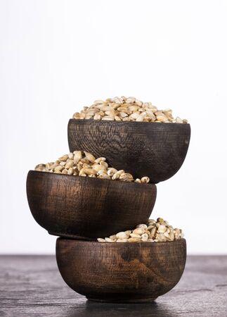 Pearl barley in three wooden bowls - Hordeum vulgare