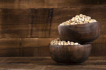 Pearl barley in two wooden bowls - Hordeum vulgare