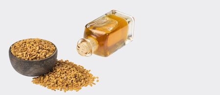 Fenugreek with oil in bottle over white background