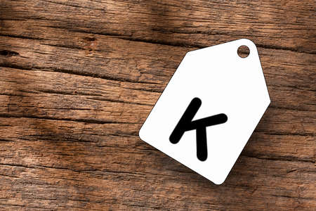 Blank label with letter K on wooden background