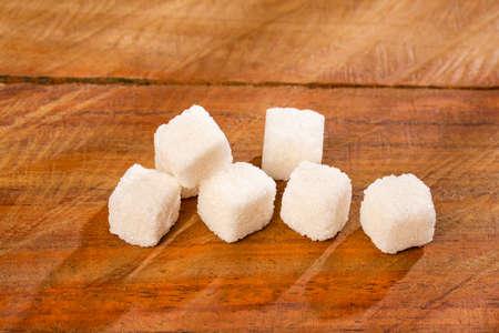 Refined sugar cubes on wooden background Standard-Bild
