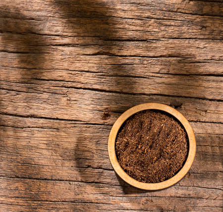 Black tea powder in wooden bowl - Camellia sinensis