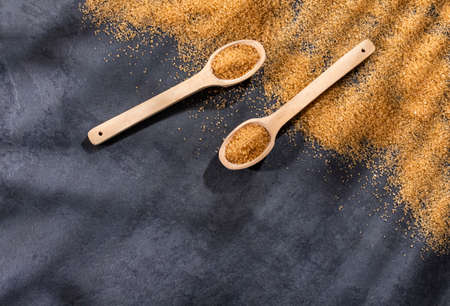 Organic brown sugar in wooden spoons - Saccharum officinarum