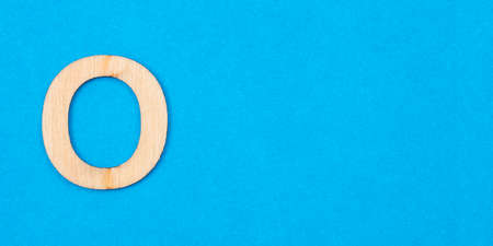 Letter O in wood on blue background