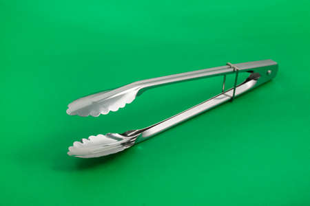 Metal kitchen tongs on green background - Text space