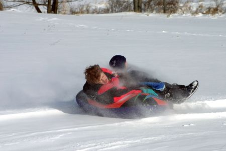 Woman and child sledding with snow spray