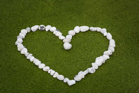 white pebble: Heart shape from white pebble stones on golf green spring colors. Love concept. Stock Photo