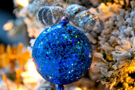 Blue sequined Christmas ball ornament hanging from an illuminated, flocked Christmas tree is a welcoming sight for a family that is home for the holidays. Фото со стока