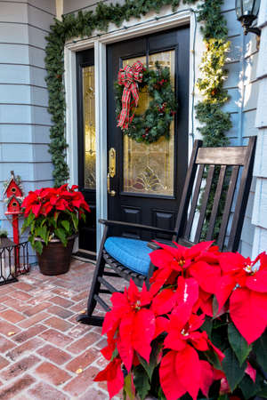 Front door entryway decorated with traditional American Christmas decor, with poinsettias, wreath, lanterns, red birdhouse, evergreens and a rocking chair.