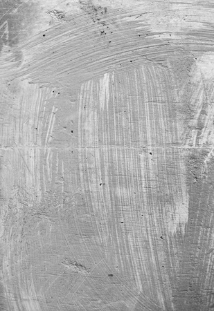 paint brush-marks on concrete. Gray on gray, loose brushmarks of a big bristle brush on uneven concrete surface. Nice grunge texture. Stock Photo