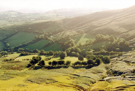 Sunlit valley (Lake District UK). Beautiful gentle green valley with golden sun, haze, and warm shadows. Yellow and green fields alternate with treelined hedgerows and wild mountain vegetation. Stock Photo