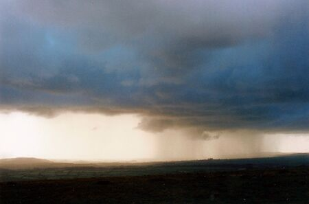Rain on the hills, gorgeous shot of rain on distant dark hills with heavy clouds over a gentle open landscape.