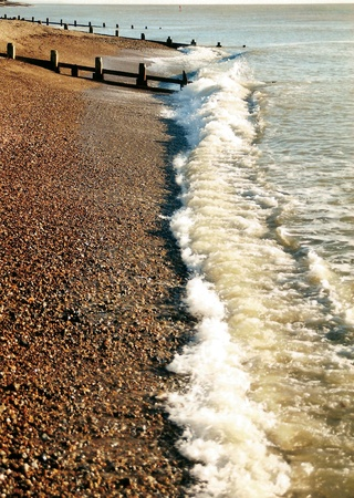 breakwaters: pebble beach, small waves on a pebble beach UK, with breakwaters, warm colors