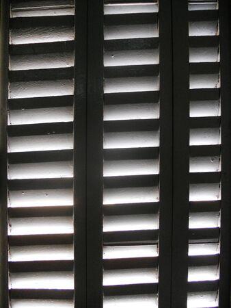 zon door rolluiken, zonlicht door houten luiken Stockfoto