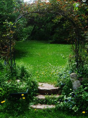 english garden: arch and steps in English garden, springtime