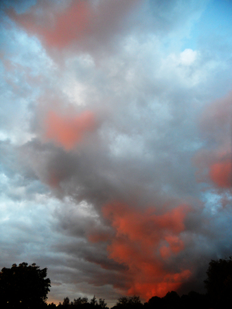Dramatic sunset reds on gray clouds Stock Photo