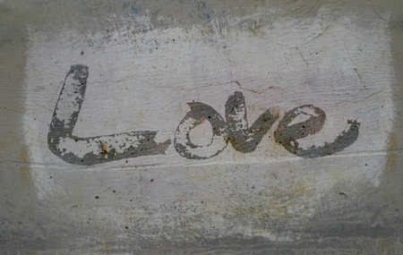 love painted, the word love hand-painted, artistic word love, rough painted partially washed-out brush lettering on grunge painted concrete texture. Imagens