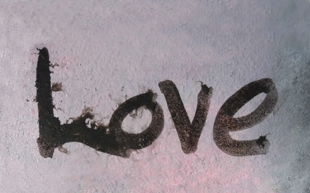 love painted, the word love hand-painted, artistic word love, brush lettering partially washed-out on wet paper with ink running on painted texture.