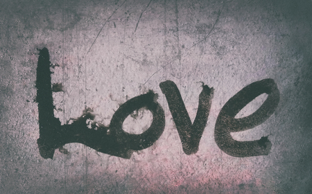 love painted, the word love hand-painted, artistic word love, brush lettering partially washed-out on wet paper with ink running on painted grunge texture, pink tints, blur vignette. Banco de Imagens