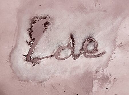 love painted, the word love hand-painted, artistic word love, brush lettering partially washed-out on wet paper with indian ink running on gray grunge painted concrete texture, pink tint.