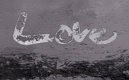 love painted, the word love hand-painted, artistic word love, rough painted partially washed-out brush lettering on grunge painted concrete texture. Banco de Imagens