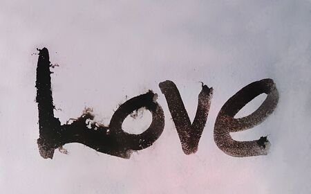 love painted, the word love hand-painted, artistic word love, brush lettering partially washed-out on wet paper with ink running on blurred painted texture.