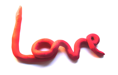 love clay, the word love hand-made in red modeling clay, love word in clay, 3D love word isolated on white (with shadows). Stock Photo