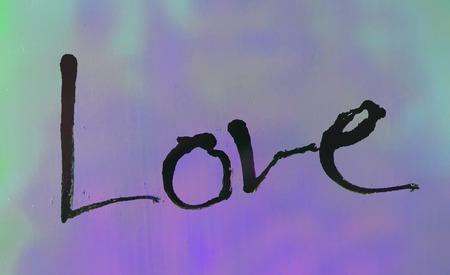 love painted, the word love hand-painted, artistic word love, rough Indian-ink brush lettering on blurred colored paint texture.