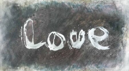 love painted, the word love hand-painted, artistic word love, pale rough painted brush lettering, partially washed-out, on rough gray painted texture.