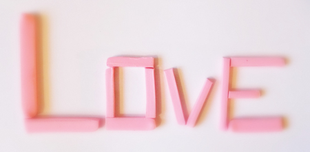 love hand-made, the word love in pink modeling clay, 3D love word, vertical view, with gradation blurs at either end, focused in the middle, pale.