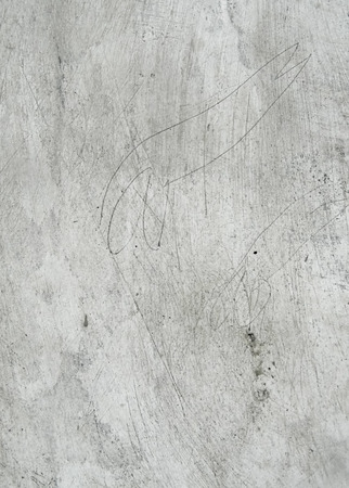 Lightly distressed plaster surface with scratches and marks, grunge background texture.