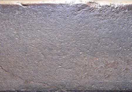 고르지 않은 거친 오래된 금속 표면, 주로 상단에 놋쇠 둥근 가장자리와 따뜻한 따뜻한 회색. 스톡 콘텐츠