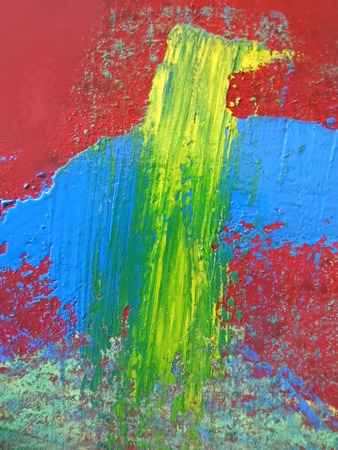 Closeup of smeared thick gauche paints and pastels texture on rough board, blue, yellow, red.