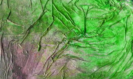 Painted organic texture made by glue crumpled tissue on painted board, bright green and purple. Stock Photo