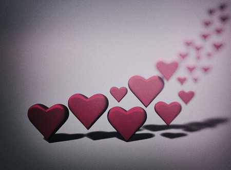 Many 3D hearts, a group of different sized red heart shapes with shadows, with dark blur vignette, pink tints. Stock Photo