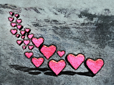Cartoon style image of many 3D hearts, a group of different sized red heart shapes with shadows, grungy cartoon sketch style, on a gray grunge texture background. Stock Photo