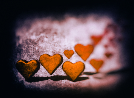 Aquatint style image of many 3D hearts, a group of different sized orange heart shapes with shadows, on a grunge textured background with warm color tints. Stock Photo