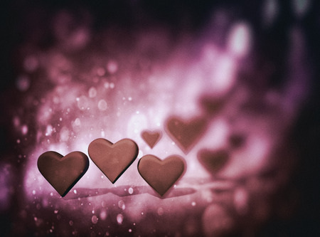 Many 3D hearts, a group of different sized heart shapes with shadows, with dark blur vignette and bokeh texture, warm color tints.