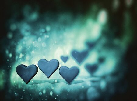 Many 3D hearts, a group of different sized heart shapes with shadows, with dark blur vignette and bokeh texture, blue and green tints.