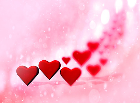 Many 3D hearts, a group of different sized heart shapes with shadows, with blur vignette and bokeh texture, red tints. Stock Photo